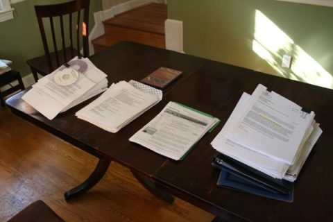 Stacks of actor headshots and acting resumes sitting on a casting directors table